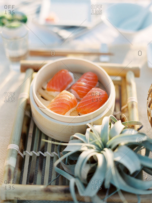 Salmon sushi in a wooden food container at an outdoor picnic