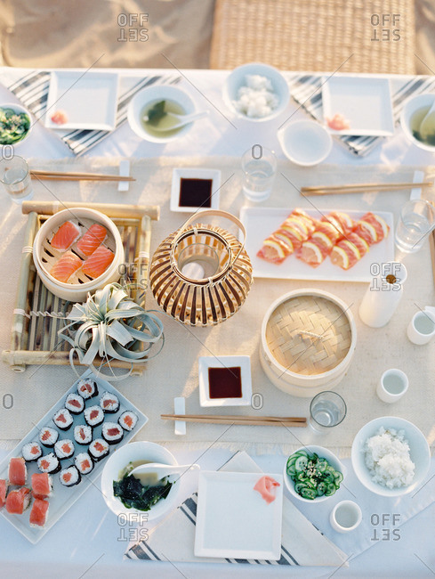 Outdoor table set with various sushi dishes