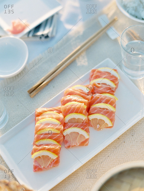 Sushi rolls with salmon and lemon wedges