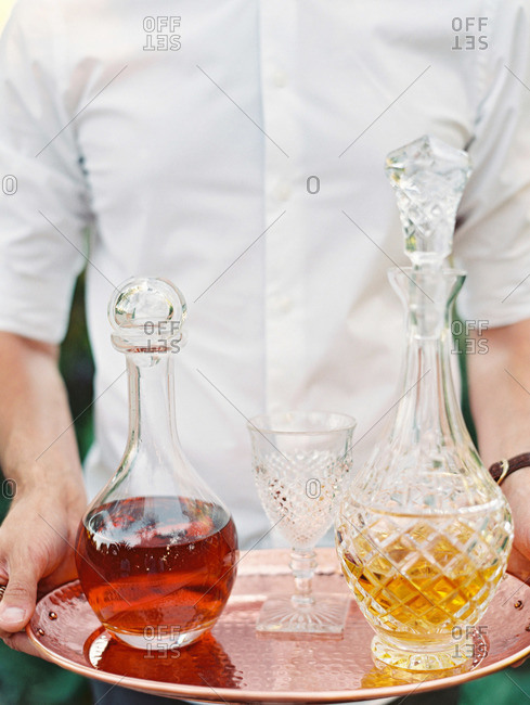 Waiter carrying a copper tray with decanters of liquor