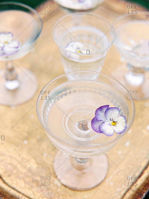 Purple and white flowers floating in water glasses