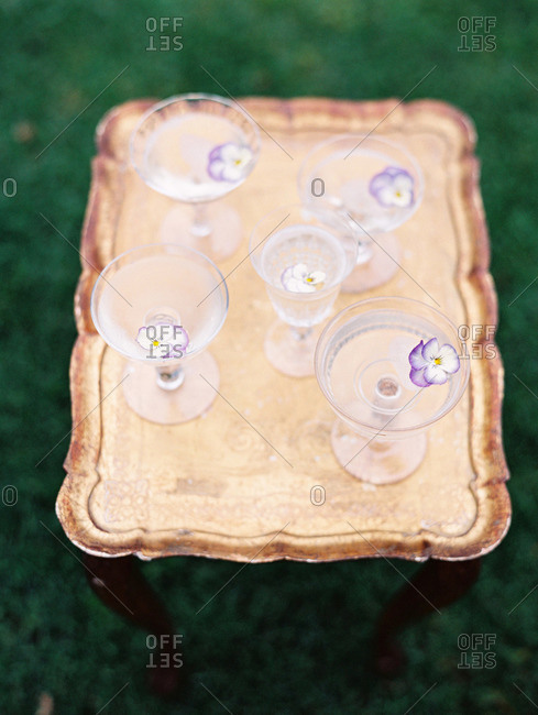 Water glasses with flowers on a gold tray table
