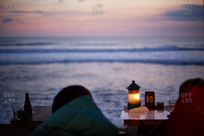 Two beachside tables facing the ocean at sunset