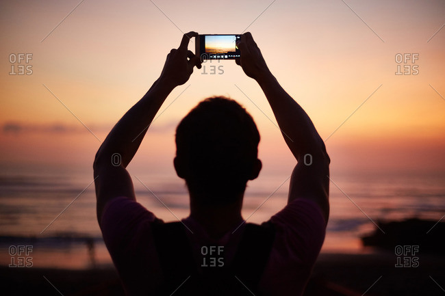 Man raising his arms to photograph the sunset with a cell phone