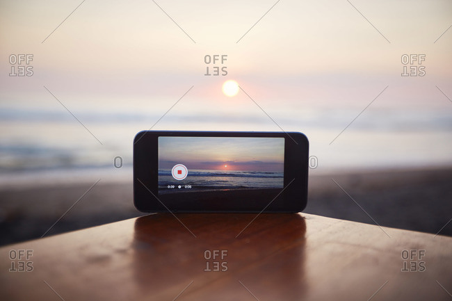 Smartphone sitting on a beachside table taking a video of a sunset