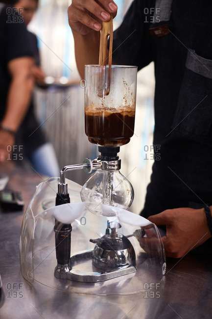 Barista using siphon coffee maker
