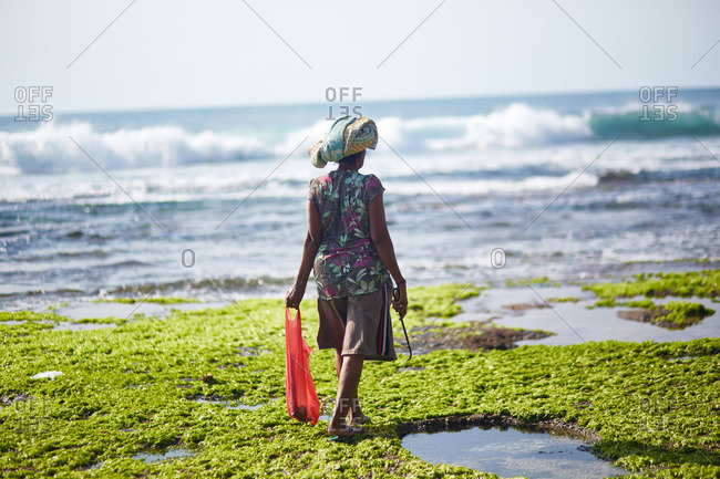 Woman walking along beach near tidal pools