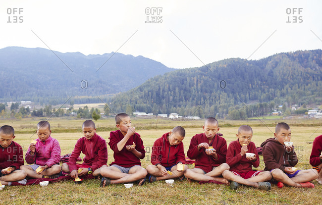 Kingdom of Bhutan - October 31, 2015: Group of young boys sitting outside in a line