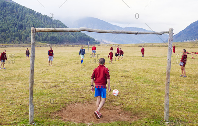 Kingdom of Bhutan - October 31, 2015: Young boys playing soccer in a rural setting