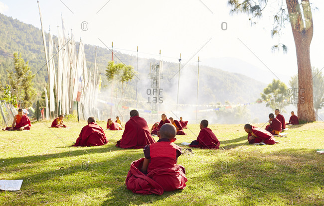 Group of young Buddhist monks sitting outside in a group