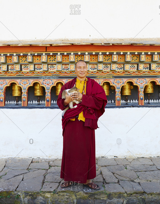 Kingdom of Bhutan - November 1, 2015: Portrait of a smiling Buddhist monk holding a cat in his arms