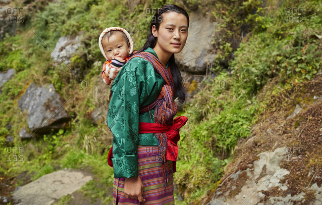 Kingdom of Bhutan - November 3, 2015: Portrait of a woman carrying her child on her back on a rugged mountain path