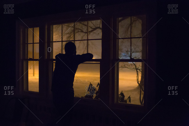 Person silhouetted at window watching snow