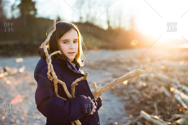 Girl holding branches outside in sunlight
