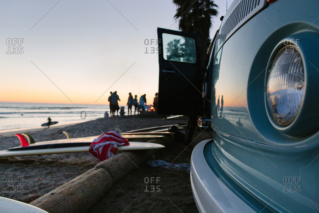 Surfboards and the front of a vintage car on a beach at sunset
