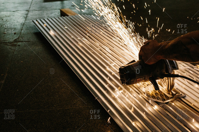 Person cutting corrugated metal with an electric saw