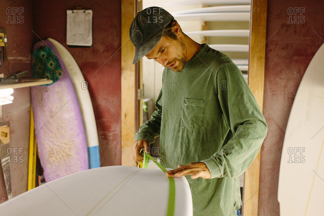Man taping off an unfinished surfboard for painting