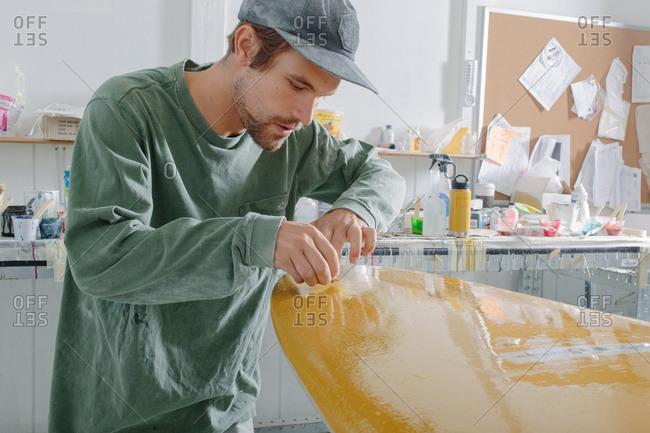 Man finishing a surfboard in a workshop