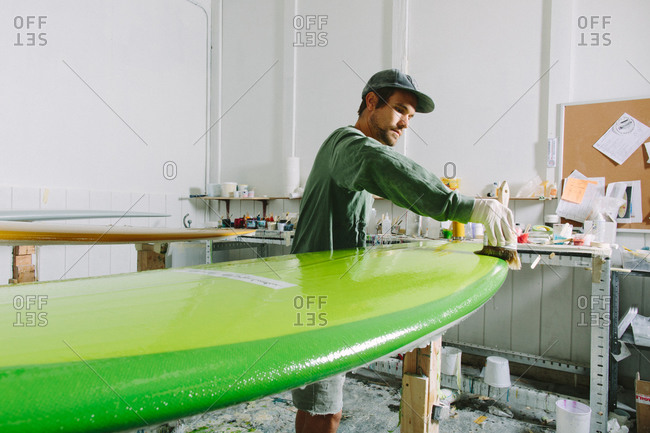 Man painting a clear protective coating on a finished surfboard