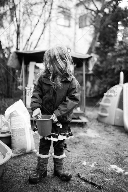 Little girl playing outside with a bucket