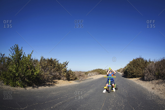 Toddler boy on tricycle on desert road