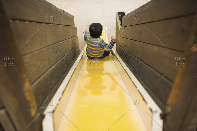Elevated view of toddler boy sliding down yellow slide