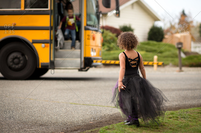 Young girl in dance costume meets her brother at the school bus stop