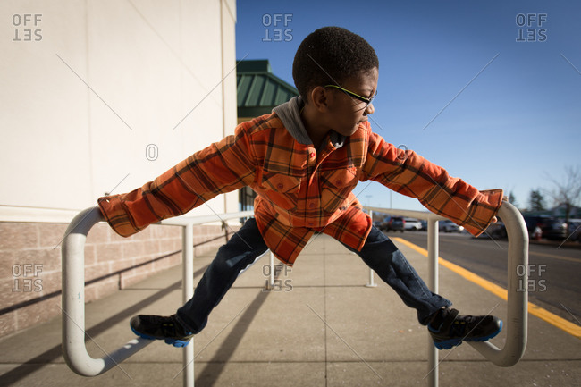 Young boy climbing on railing at shopping center