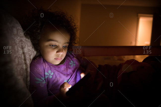 Young girl playing on electronic device