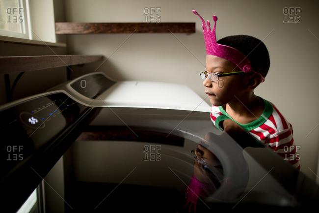 Boy wearing crown watches washing machine