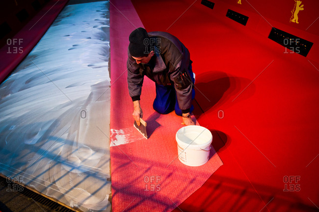 Berlin, Germany - February 5, 2014: A worker spreading glue for the red carpet outside the Potsdamer Platz Theatre