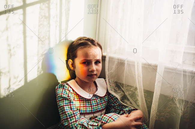 Girl in an old fashioned dress sitting in the corner near a window