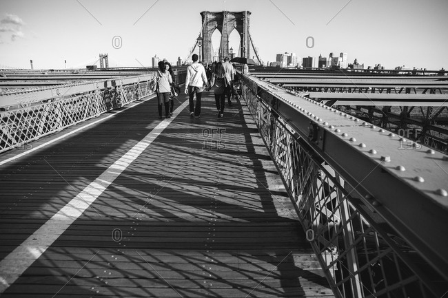 People walking across a section of the Brooklyn Bridge Promenade