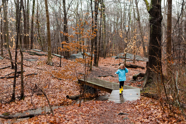 Girl walking along a foot bridge in the woods on a wet autumn day