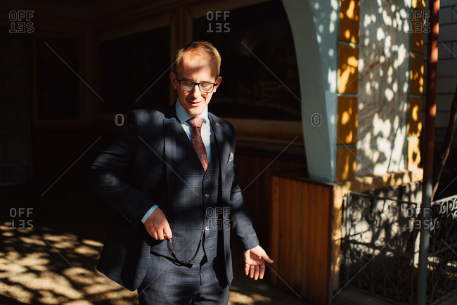 Groom tucking his pocket watch into his suit's vest pocket