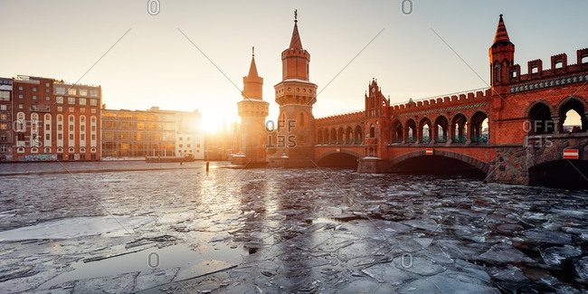 Oberhaum Bridge over Berlin's River Spree with ice at sunset