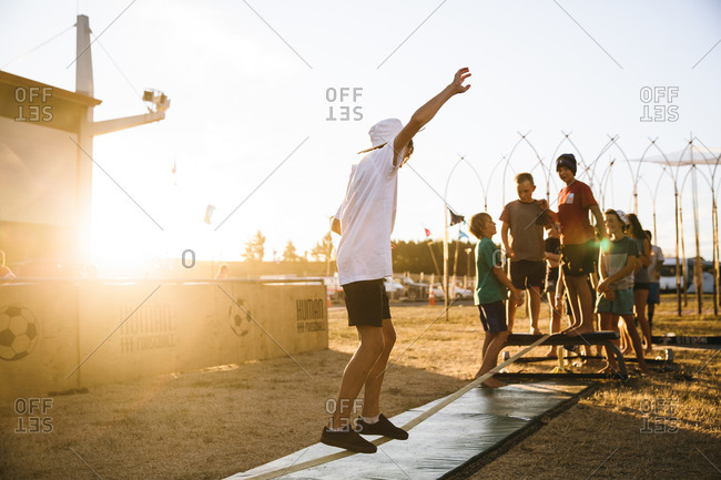 Hamilton, New Zealand - January 30, 2016: Boy walking along a slack line music festival  while a group of friends look on