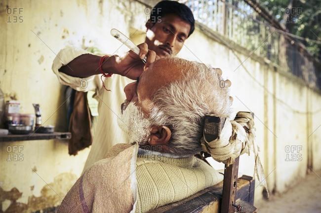 Delhi, India - November 18, 2012: Indian barber giving man a shave