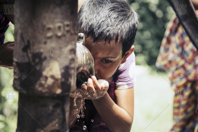 Forbesganj, Bihar, India - July 2, 2015: Boy drinking from water pump, India