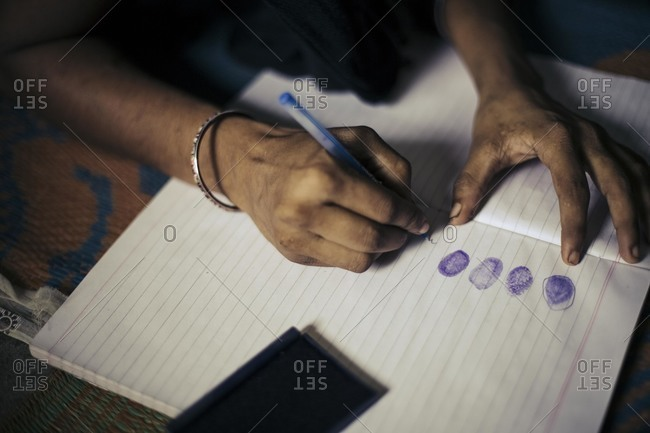 Indian woman using fingerprint to sign name
