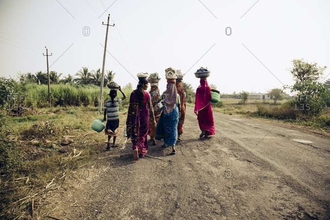Bagalkot, Karnataka, India - December 15, 2014: Women carrying laundry on heads, India