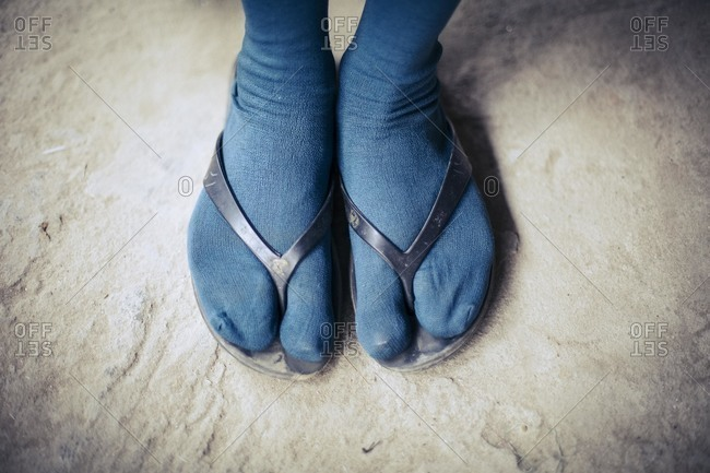 Feet in flip flops and socks