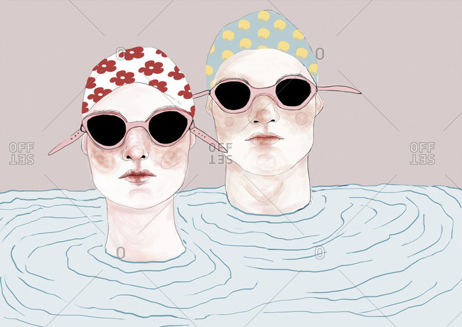 Two swimmers wearing goggles with their heads above water