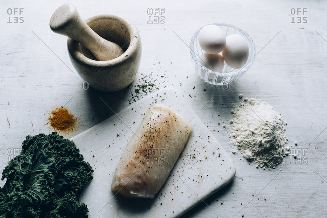 Overhead view of a raw white fish filet on a cutting board next to kale, eggs, and a mortar and pestle