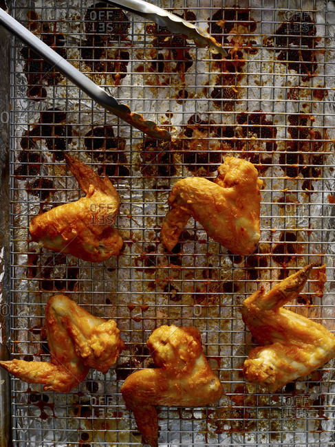 Overhead view of buffalo chicken wings on a wire cooking grate