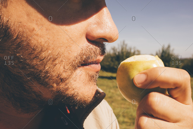 Close-up of a man holding a freshly bitten apple under his nose