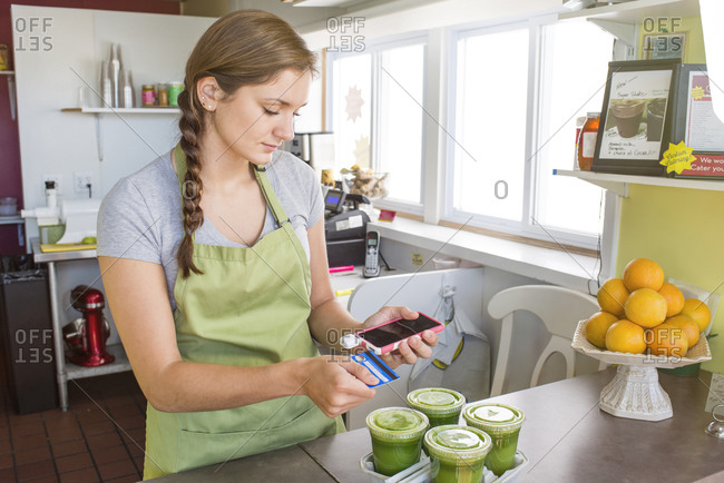 Woman working in a juice bar using an electronic payment service on a smart phone