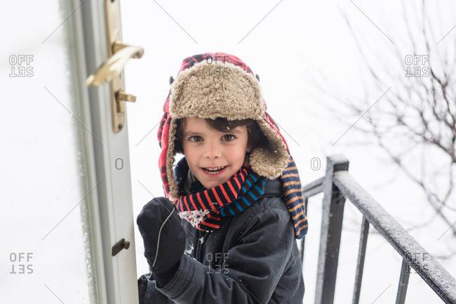 Boy opening front door to come inside during snowy weather