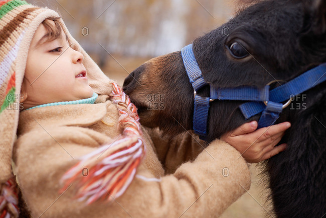 Girl in a winter overcoat recoiling from a curious pony