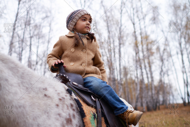 Girl in a winter overcoat sitting on a saddle